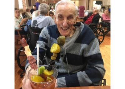 Elderly Man Smiling Holding his Drink