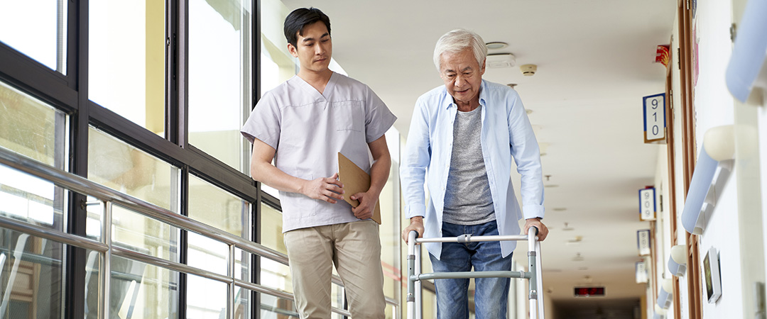 Elderly Man Being Assisted by Male Nurse