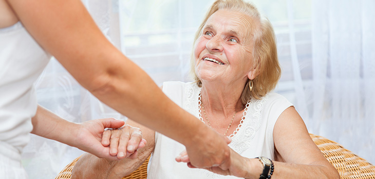 Elderly Women Smiling While Being Helped