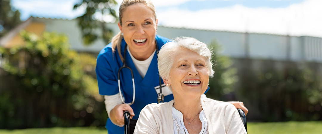A nurse taking a patient out for a stroll.
