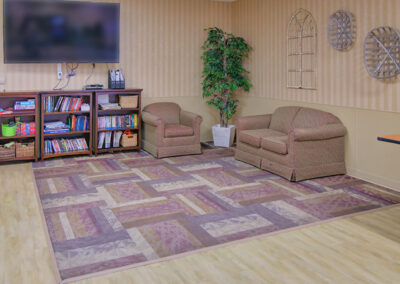 Common area with books, seating and a television.