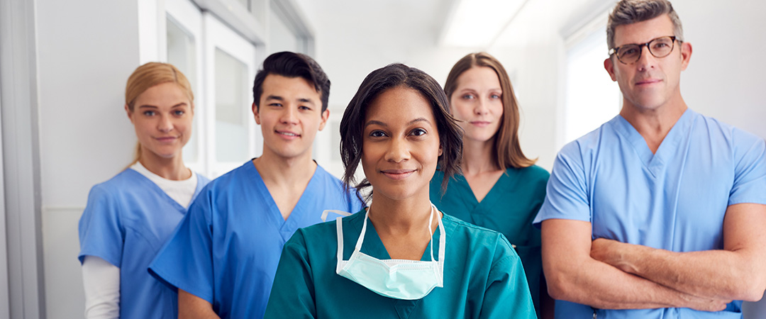 Medical staff dressed in scrubs standing in a hallway